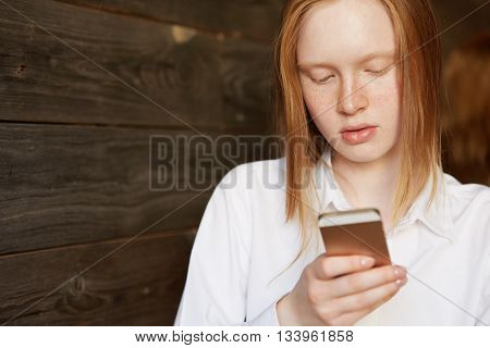 Portrait Of Young Blond Caucasian Girl With Ivory Skin And Freckles. Business Lady Looking Down At H