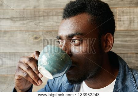 Close Up Half Profile Of African American Designer Or Writer, Enjoying Morning Cappuccino, Sitting A