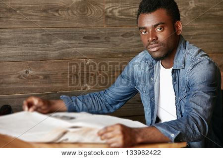 Selective Focus. Young African Student Sitting At The Wooden Table At A Coffee Shop While Waiting Fo