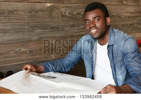 Attractive Young African Office Worker In Denim Jacket Reading Tabloid While Sitting At The Wooden T