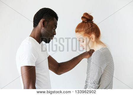 A Touching Scene Of African American Man Comforting Young Redhead Girl. He Put His Arm On Her Should