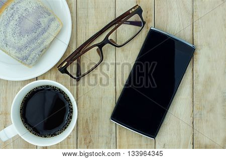 Smartphone eyeglasses and a cup of coffee with bread on wooden background. Working in morning concept.