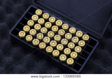 9 mm ammunition bullets put in a box on the table.