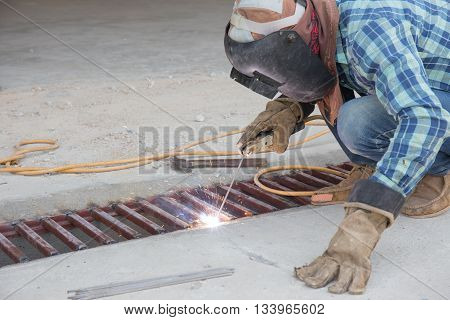 worker protect himdelf from flash and spark from welding metal at construction site