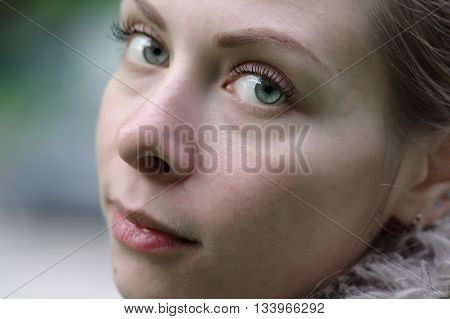 Cropped portrait of a young looking romantic and calm woman outdoor shot with particular focus