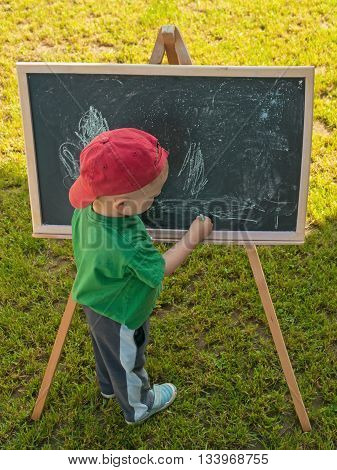 young boy with a blackboard on green grass