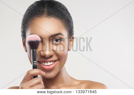 Portrait of attractive mulatto young woman covering her eye with a make-up brush. She is looking at camera and smiling. Lady is standing with bare shoulders. Isolated and copy space in right side