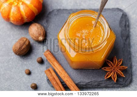Pumpkin confiture jam sauce with spices on stone table Top view.