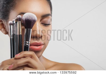 Portrait of beautiful young mulatto woman holding a set of make-up brushes near her face. She is standing and looking down with sensuality. Isolated and copy space in right side