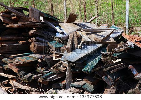A pile of debris and old broken wooden boards after demolition of the house