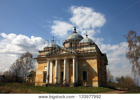 old orthodox church in classical style with classical white portico and yellow shabby walls and grey dome