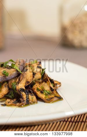 Eggplant with olive oil and parsley in a white plate