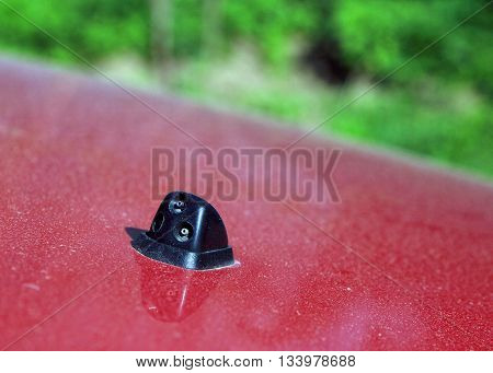 black plastic injector washer on red car hood