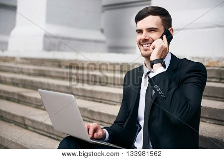 Nice to hear you. Pleasant handsome smiling businessman sitting on the footsteps and using laptop while talking on cell phone