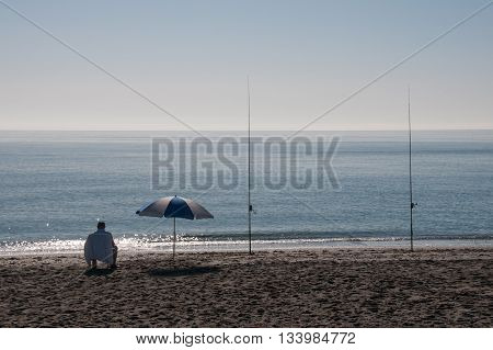 Lone surf fisherman sitting in a chair next to an sunshade at a beautiful beach on a sunny day doing fishing