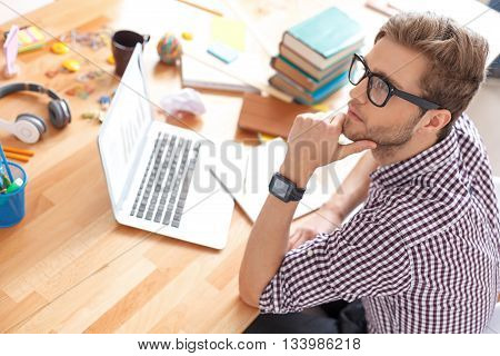 Working hard at his studies. Top view of guy thinking about solution of task, using laptop