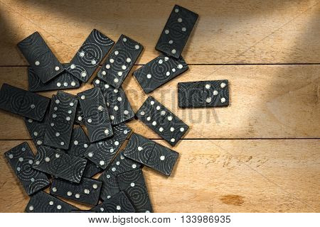 Top view of a group of old wooden pieces of the domino game on a wooden table with shadows