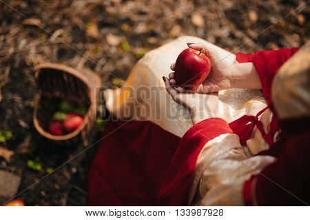 Woman holging an apple. Witch from fairy tale Snow White