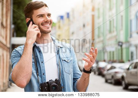 Real chatter box. Positive delighted smiling man holding cell phone and talking on it while having a walk