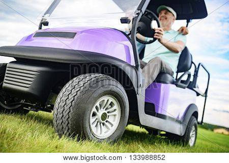 On his way to the next hole. Close up of golf car wheel driving by handsome smiling man with his son