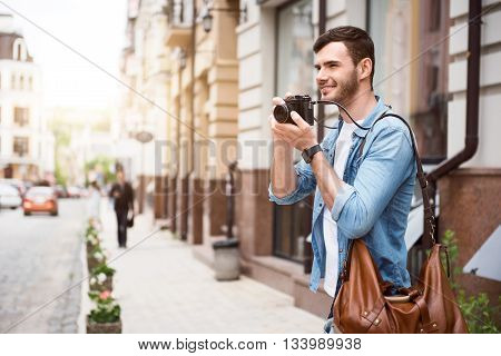 Real photographer. Positive elated smiling man holding camera and taking photos while having a walk