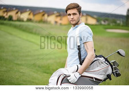 Ready for day on course. Serious young man standing on golf course with golf bag, ready for day on course