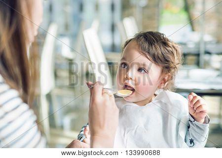 Mum spoon-feeds her child