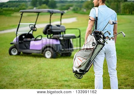 Ready for that hole in one. Close up of male golfer walking away while holding golf back, standing on green golf course with golf cart on background