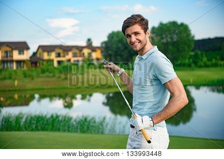 Golfers aspirations. Smiling young golfer looking at camera while holding his club, standing on golf course