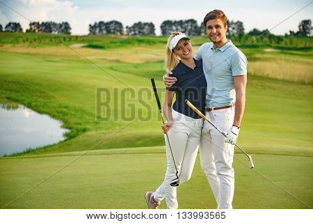 Tee time. Attractive young couple with their golf clubs, standing on green course and smiling