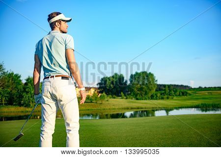 Confident golfer. Young male golfer holding driver and looking at camera while standing on green