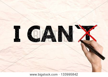 I can self motivation concept. Businessman crossing out letter 'T on crumpled paper so that it reads i can