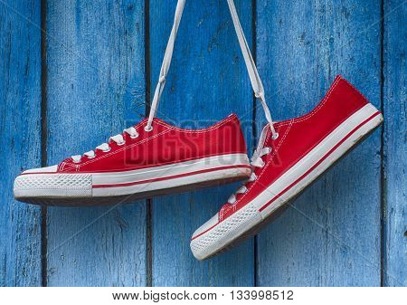 pair sneakers hanging on a wooden old retro blue background