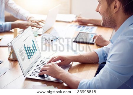 Work with pleasure. Positive handsome delighted man sitting at the table and using laptop while working with his colleagues