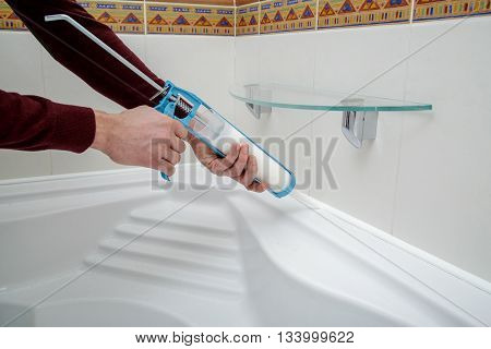 Worker hands applying silicone sealant with caulking gun.
