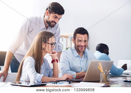 Work with positivity. Cheerful delighted smiling colleagues using laptop and working in the office while expressing gladness