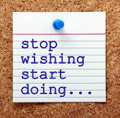 The words Stop Wishing Start Doing in blue text on a note pinned to a cork notice board as a reminder poster