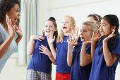 Group Of Children With Teacher Enjoying Drama Class Together poster