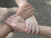 Man and women join hand together on the street under sunlight in the afternoon (Teamwork concept) poster