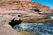 Pot Alley's natural sandstone recess with Indian Ocean waters and sandstone cliffs under clear blue skies in Kalbarri, Western Australia. poster