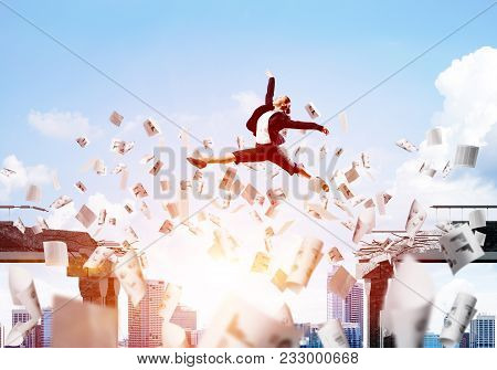Business Woman Jumping Over Gap With Flying Paper Documents In Concrete Bridge As Symbol Of Overcomi
