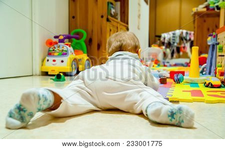 Back View Of A Baby Boy Surrounded By Toys In His Room, Playing With Them.