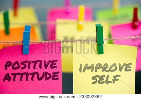Positive Attitude And Improve Self Written In Pink And Yellow Sticky Notes Are Clipped To The Rope