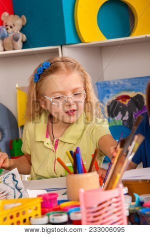 Small students painting in art school class. Child drawing by paints on table. Boy and girls in kindergarten. Best choice of brushes for watercolor painting. Art children's school.