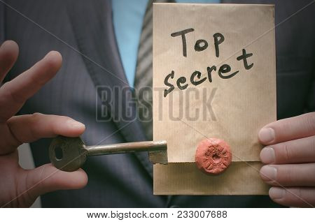 Top Secret Concept. Top Secret Documents Or Message And A Decryption Key In Businessman Hands. The A