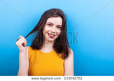 Smilng Woman Playing With Her Hair On Blue Background