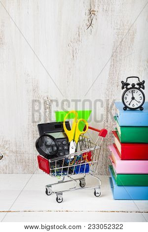 Items For School In A Shopping Trolley,alarm Clock And Books On A Wooden Background. Concept Of Buyi