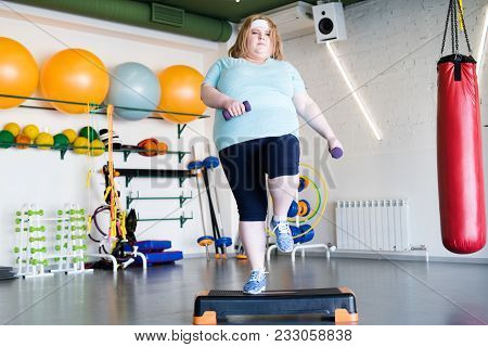 Full Length Portrait Of Obese Young Woman Doing Strep Exercises With Weights In Fitness Club, Copy S