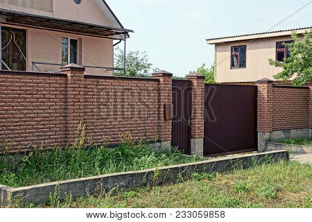 Part Of A Brown Brick Fence And Closed Door On The Street