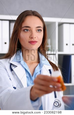 Beautiful Smiling Female Doctor Hold In Arms Pill Bottle And Offer It To Visitor Portrait. Panacea O